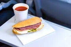 Inflight mål för ekonomiklass, smörgås och tomatfruktsaft på den hopfällbara tabellen Arkivbild