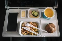 Inflight meal service tray for economy class, meat with pasta, seasoning fruit, salad, cucumber, a glass of juice and butter. Selective focus royalty free stock photo