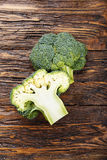 Inflorescence of broccoli on a wooden table. Inflorescence of raw broccoli on a wooden table, vertical photo Stock Images