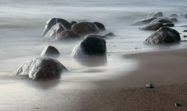 Inflow of a wave with stones on sand Stock Photography