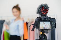 Influencer женского блоггера онлайн держа хозяйственные сумки и серии одежд на одеждах кладут на полку для записывать новое видео стоковые изображения rf