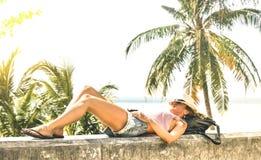 Influencer di viaggio della giovane donna che si rilassa sulla parete di pietra alla passeggiata della spiaggia di Phuket - conce fotografia stock