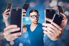 Influencer holding an exaggerated number of smartphones. Young man with 6 arms is holding 6 smartphones to take a selfie. Abstract digital background with bokeh royalty free stock image