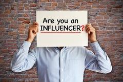 """Influencer marketingowy pojęcie z """"are ty influencer† pytanie na białej księdze w młodych blogger's rękach obraz royalty free"""