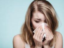 Influensaallergi Sjuk flicka som nyser i silkespapper hälsa royaltyfria foton