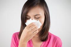 Influensaförkylning eller allergitecken Sjuk kvinnaflicka som nyser i silkespapper Arkivfoton