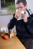 Influenza. Man with influenza, sneezing in a handkerchief Stock Images