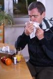Influenza. Man with influenza, sneezingn in a handkerchief Stock Photos