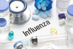 Influenza. Concept photo with pills, syringe, vials, and stethoscope Royalty Free Stock Photo