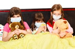 Influenza Among Preschoolers. Sick children in bed wearing medical masks because of infection with influenza virus Stock Photos