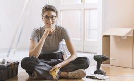 Inflyttning för ung kvinna hennes nya hus och göra en hem- makeover royaltyfri fotografi