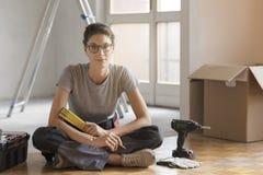 Inflyttning för ung kvinna hennes nya hus och göra en hem- makeover arkivbilder