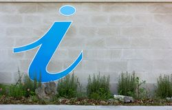 Info Sign on an Exterior Wall. Blue information sign on the exterior wall over a flowerbed Stock Photography
