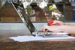 Informação entrando do homem de negócios de um cartão de crédito usando o portátil Imagem de Stock