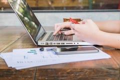 Informação entrando do homem de negócios de um cartão de crédito usando o portátil Fotografia de Stock Royalty Free
