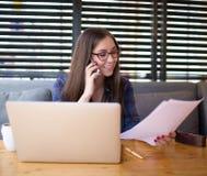 Informação especializada de sorriso da leitura do editor da mulher nos originais de papel e fala no telefone celular imagem de stock royalty free