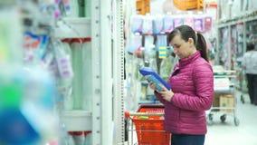 Informações sobre o produto de leitura da mulher no supermercado video estoque