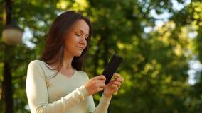 Información de la lectura de la mujer en smartphone almacen de metraje de vídeo