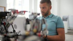 Información que mecanografía del ingeniero de sexo masculino sobre el robot en el ordenador portátil