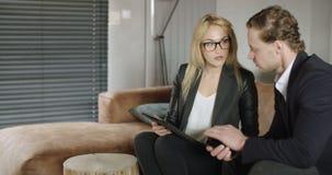 Informal business meeting. Businessman sit and have informal meeting looking at data on digital tablet. Business woman using digital tablet on business meeting stock video footage