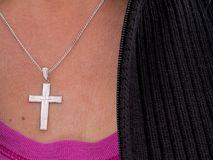 Woman wearing cross and chain, Christian religious symbol. Stock Image