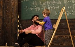 Informal education concept. Kid playing with mustache of dad or teacher. Having fun at the lesson.  royalty free stock photo