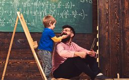 Informal education concept. Kid playing with mustache of dad or teacher. Having fun at the lesson.  royalty free stock photos