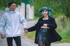 Informal girl with blue hair and a man with pale skin at the street walking. Informal girl with blue hair and a men with pale skin at the street walking and Royalty Free Stock Photo