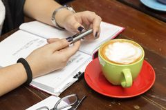 An informal meeting: cup of coffee, notebook, hands and a pen on the table, close up stock image