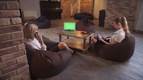 Informal meeting of two women. Women sitting bean bag chairs. One of them speaking by phone another  using tablet stock video footage
