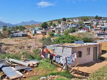 Informal settlement in South Africa with solar panels. Informal settlement - Enkanini with mountain and blue sky on the outskirts of Stellenbosch, Western Cape Royalty Free Stock Photos