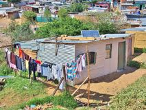 Informal settlement in South Africa with solar panels. Solar panels on the roof of shack at Informal settlement - Enkanini, on the outskirts of Stellenbosch Stock Photo