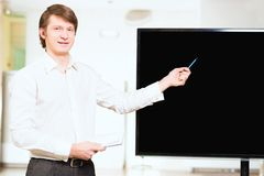 Informally dressed businessman shows blank screen Royalty Free Stock Image