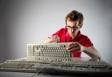 Informatics. Young informatics guy repairing old keyboard Royalty Free Stock Photography
