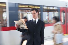 Information. Businessman reading the newspaper at the train station Stock Photography
