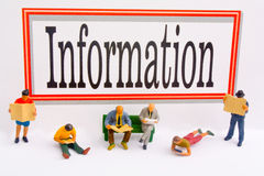 Information. Miniature figures reading in front of an information sign Stock Photography