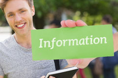 Information against handsome student smiling at camera outside on campus stock photography