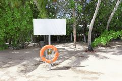 Information board with flotation ring on beach. At tropical resort stock image