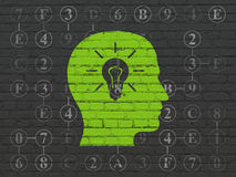 Information concept: Head With Light Bulb on wall. Information concept: Painted green Head With Light Bulb icon on Black Brick wall background with Scheme Of Stock Image