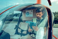 Attentive serious guy with black bearded sitting in the helicopter royalty free stock photo