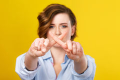 This information is not for you. Forbidden subjects. Young beautiful woman is showing forbid gesture while standing against yellow background stock photos