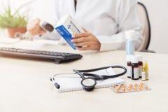 Information om läkarbehandling för kvinnlig doktor är skrivande in in i datoren, där olika droger på tabellen arkivfoton