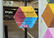 Information plaque for `Super Deluxe`, a mural by Ricardo Paniagua in the West Village, Dallas, Texas. Pictured is the information plaque for a colorful royalty free stock photos