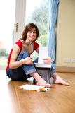Information Security. Young woman sat on the floor shredding documents Royalty Free Stock Photo