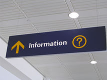 Information sign. Blue Information Sign with yellow arrow and question mark over white ceiling at airport departures hall Stock Photo