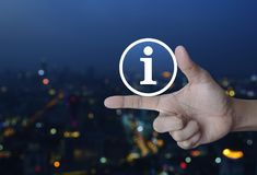 Information sign icon. On finger over blur colorful night light city towerr, Business communication concept Stock Photo