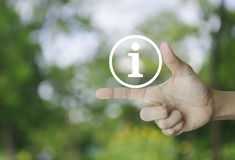 Information sign icon. On finger over blur green tree background, Business communication concept Stock Photos