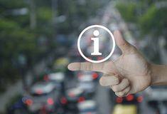 Information sign icon. On finger over blur of rush hour with cars and road, Business communication concept Stock Image