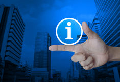 Information sign icon. On finger over modern office city tower, Business communication concept Stock Photography