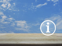 Information sign icon. On wooden table over blue sky with white clouds, Business communication concept Stock Photo